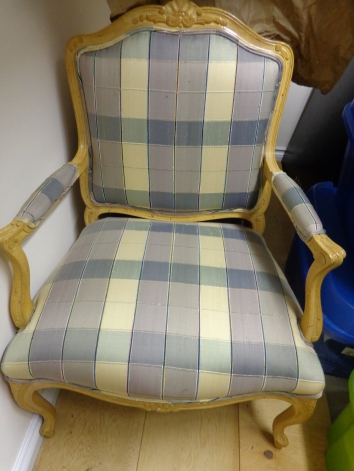 The chair has a large back and is covered in blue and yellow plaid material. The chair has wooden handles, and floral details along the top, bottom, and handles.