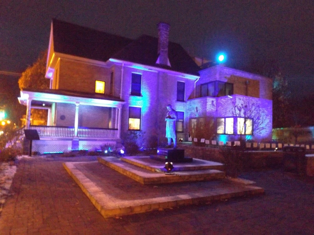 Banting House NHSC lit in blue light. The house is behind a statue of Dr. Banting located in the square outside of the house.