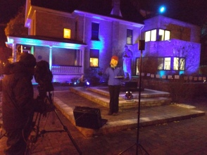 A photo of Julie Atchison, weather reporter at CTV London. She is in front of Banting House NHSC which is lit up blue for World Diabetes Day. There is also a camera-man set up to film Julie.