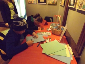Two children at a table using markers and construction paper to make birthday cards.