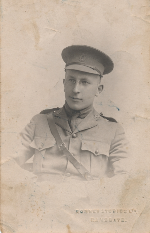 This photo shows Dr. Frederick Banting in uniform during the First World War. The page is beige in colour, and shows Banting sitting down. He is wearing his military shirt with a piece stretching from his right to left shoulder, and is also wearing a cap.