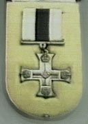 The medal is a silver cross with detailing on the points and in the middle. The ribbon has three stripes of white, black, and white. It is sitting on a cushion.