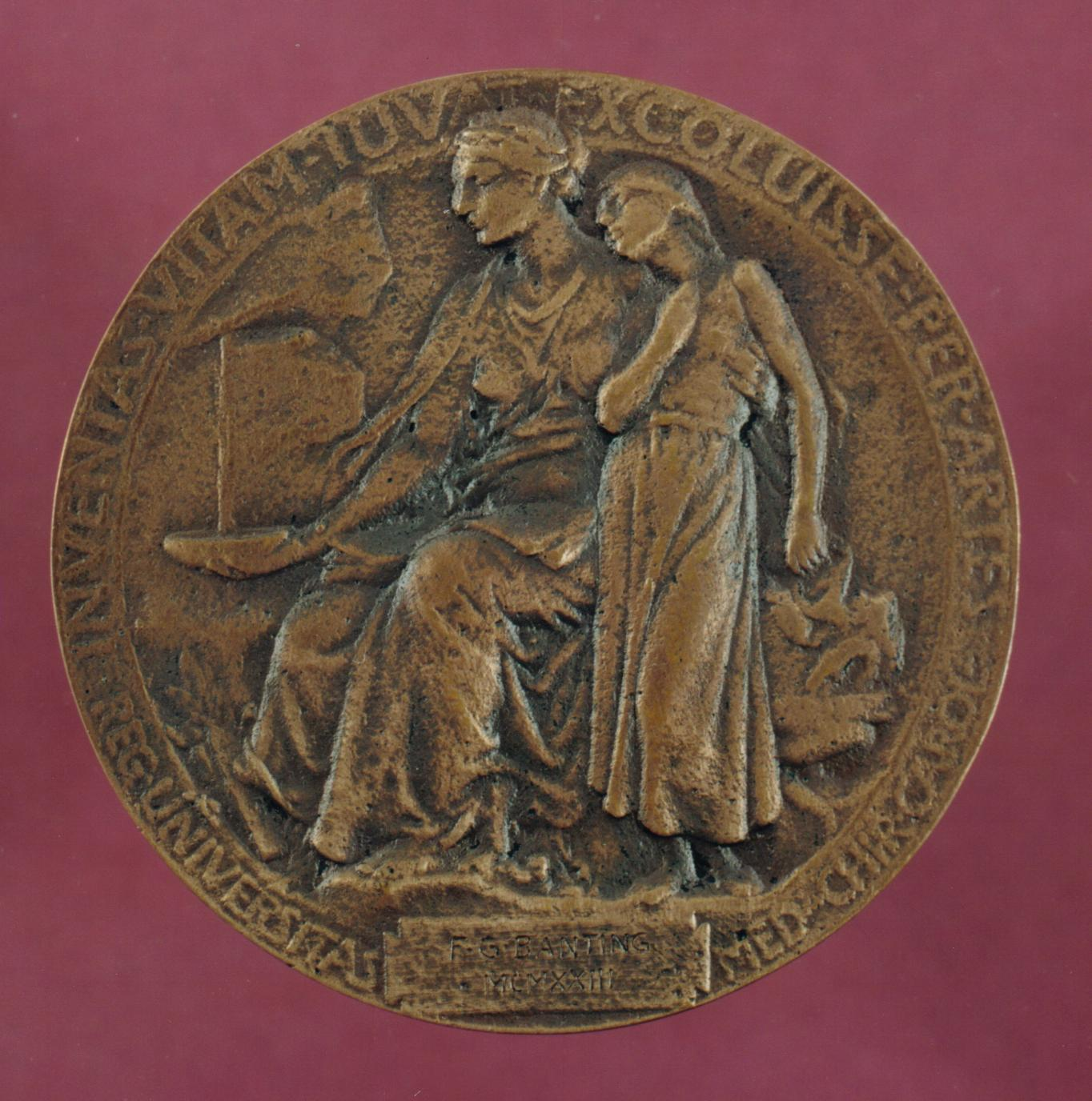 """The replica is sitting on top of a red cushion. The image on the medal is of two women, one older who is sitting and one younger who is standing. The inscription at the bottom of the medal reads, """"F.G. Banting MCXXXIII""""."""