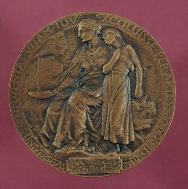 "The replica is sitting on top of a red cushion. The image on the medal is of two women, one older who is sitting and one younger who is standing. The inscription at the bottom of the medal reads, ""F.G. Banting MCXXXIII""."