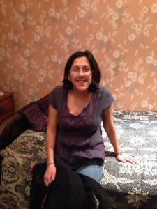 A woman wearing a purple shirt and jeans sitting on Sir Frederick Banting's bed. The wallpaper in the background is pink with white flowers on it.