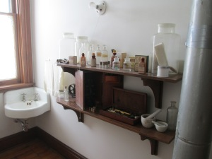 The photo shows the sink in the Apothecary room at Banting House and two shelves holding medicine bottles, vials, and supplies, as well as pestle and mortar bowls.