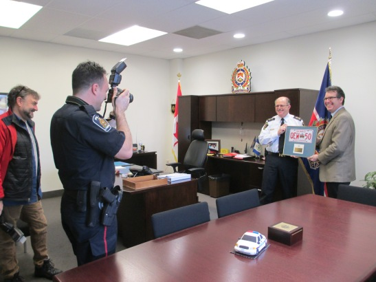 Two men with cameras taking pictures of police chief presenting a framed license plate to Grant.