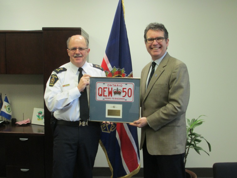 Police chief presenting framed license plate to Grant in front of the London Police Service flag and beside a wooden desk.