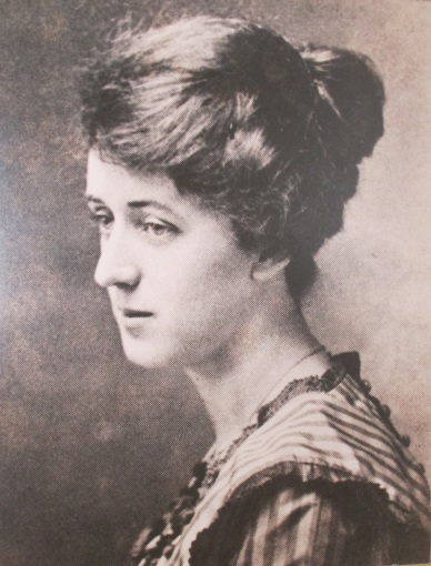 The photo shows a woman from the bust up. She is wearing a dress with stripes on the collar and her hair is pinned back in a bun.
