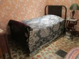 There is a bed with a metal frame, headboard, and footboard. It is covered in a blanket that has a blue and white pattern. There is pink wallpaper with flowers behind the bed. The linoleum floor is green and yellow with red flowers.